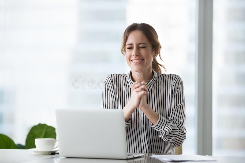 Excited businesswoman wishing for business success or celebrating victory. Enjoying new opportunity sitting at workplace with laptop, motivated female worker royalty free stock photo