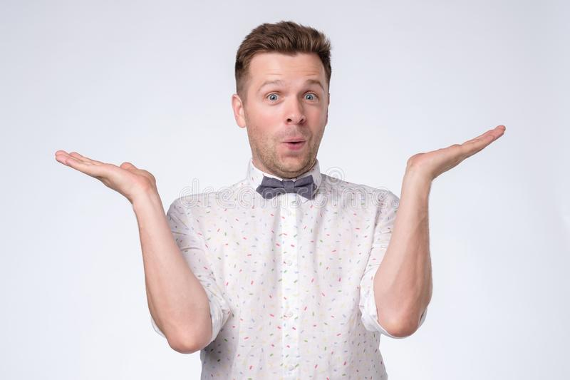 Excited casual man standing with raised hands near face stock image