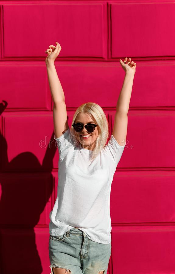Excited casual woman in sunglasses against red wall stock photo