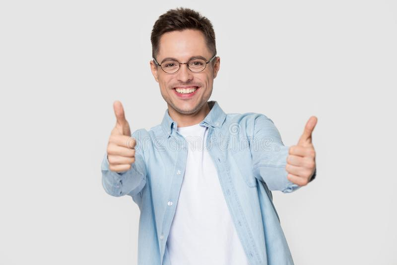 Excited Caucasian man in glasses isolated show thumbs up. Excited young Caucasian man student in glasses and shirt show thumbs up recommending service, happy royalty free stock image