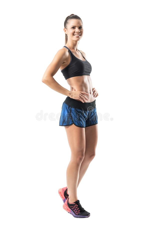 Excited cheerful fit gym woman in sportswear posing and smiling at camera. Full body length portrait isolated on white studio background stock photos