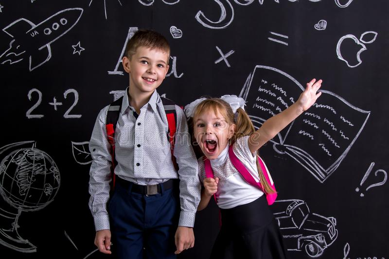 Excited and cheerful schoolkids standing before the chalkboard as a background with a backpack on their backs showing royalty free stock image