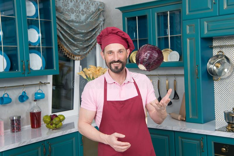 Excited chef throwing cabbage up and smiling. Emotional enthusiastic professional cook wearing chefs hat and an apron while talking about his recipe in the royalty free stock photo
