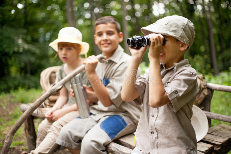 Excited children on a camping trip. Young boy explores the nature with binoculars stock image