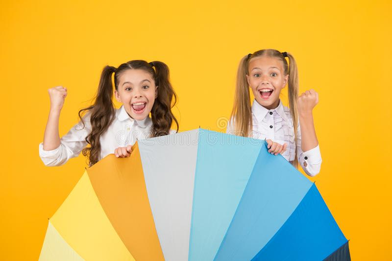 Excited children. Girls friends with umbrella. Rainy day. Happy childhood. Kids happy with umbrella. Fall weather royalty free stock images