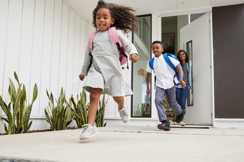 Excited Children Running Out Of Front Door On Way To School Watched By Mother stock photos
