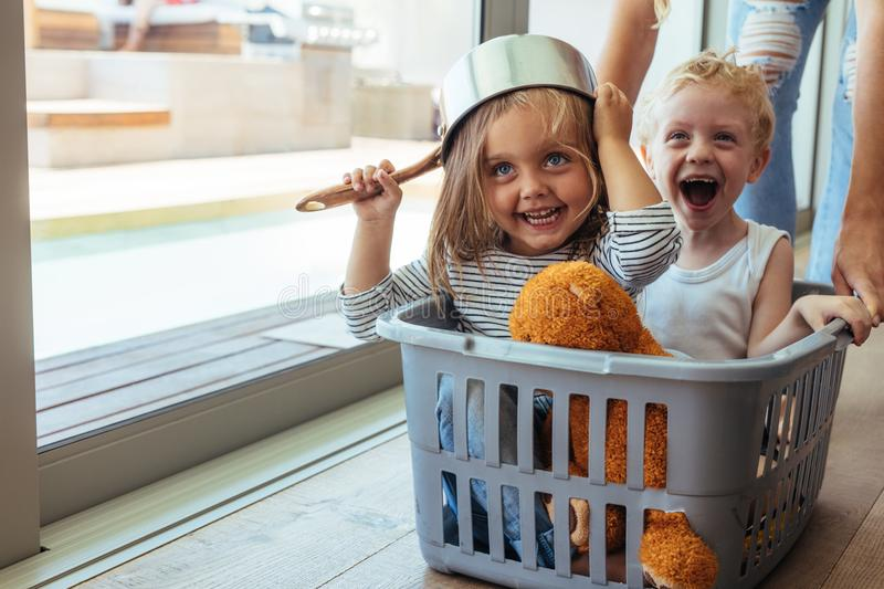 Kids rides in a laundry basket. Excited children sitting in a washing basket being pushed by mother. Girl wearing a bowl as helmet with boy laughing royalty free stock images