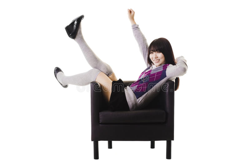 Excited Chinese student in a leather chair. stock photography