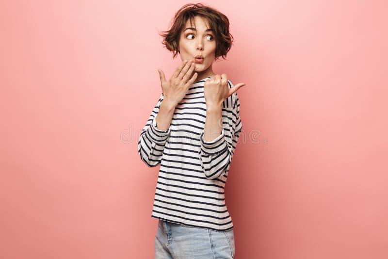 Excited chockade förvånat härligt posera för kvinna som isolerades över rosa peka för väggbakgrund royaltyfria bilder