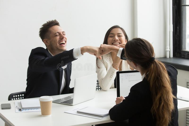 Excited colleagues giving fists bump celebrating success royalty free stock image