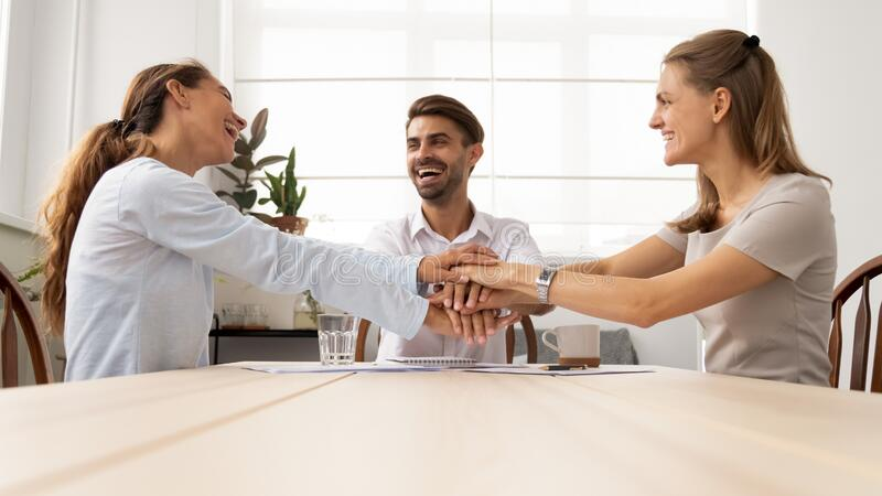 Excited colleagues joining hands, celebrating business success at meeting royalty free stock photos