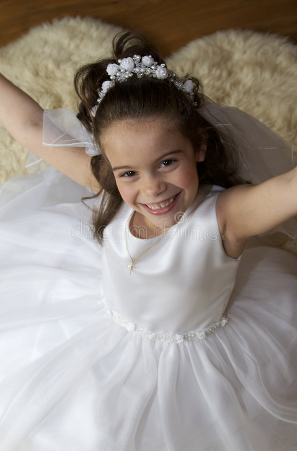 Excited Communion Girl. Portrait of a little girl in communion dress and veil stock photo