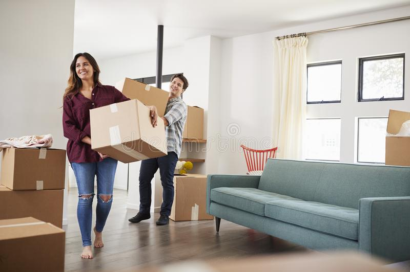 Excited Couple Carrying Boxes Into New Home On Moving Day stock photography