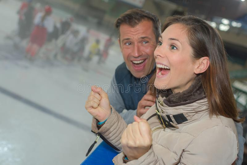 Excited couple cheering on ice hockey team. Ice royalty free stock photography