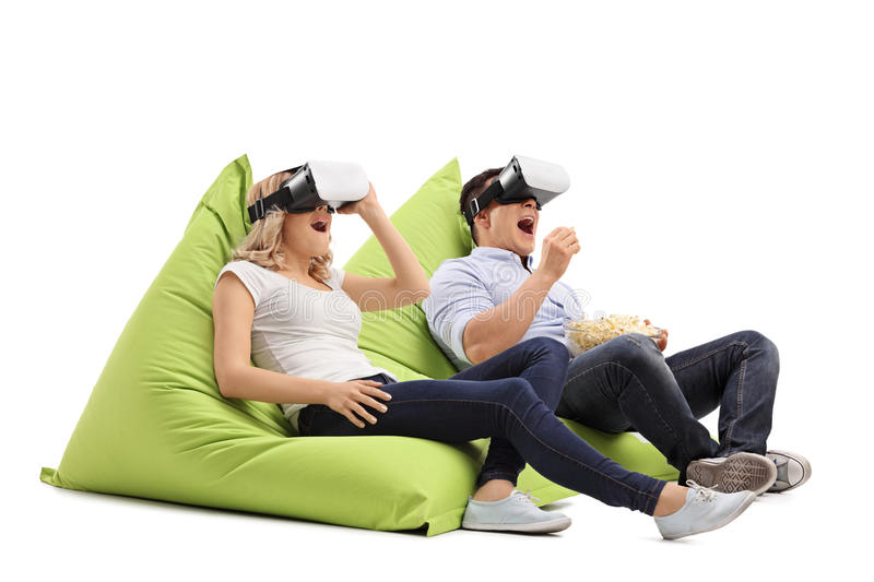 Excited couple experiencing virtual reality. Excited young couple experiencing virtual reality seated on beanbags isolated on white background royalty free stock image