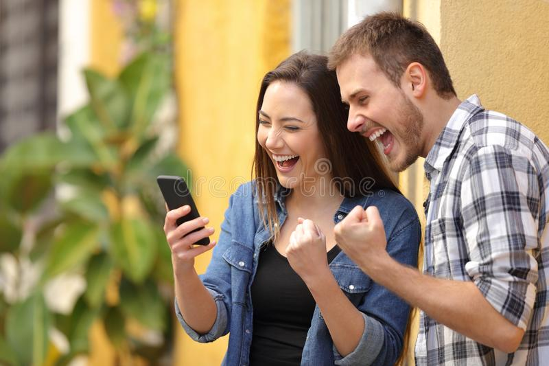 Excited couple finding online offers on phone in the street. Excited couple finding online offers on smart phone in a colorful street stock images