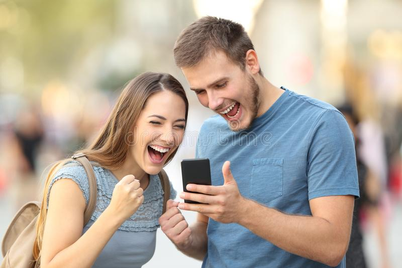 Excited couple receiving good news on line outside. Excited couple receiving good news on line in a smart phone outside on the street royalty free stock image