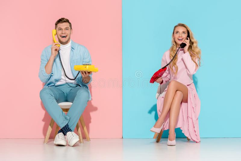 Excited couple sitting and having conversation on vintage telephones. With pink and blue background stock photography