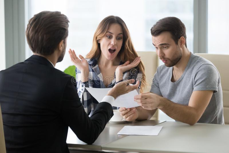 Excited couple surprised by great house purchase deal. Amazed couple surprised by unbelievable offer made by realtor or agent, excited millennial men and women stock photo