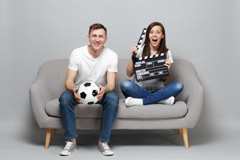 Excited couple woman man football fans cheer up support favorite team with soccer ball holding classic black film making. Clapperboard isolated on grey stock photos