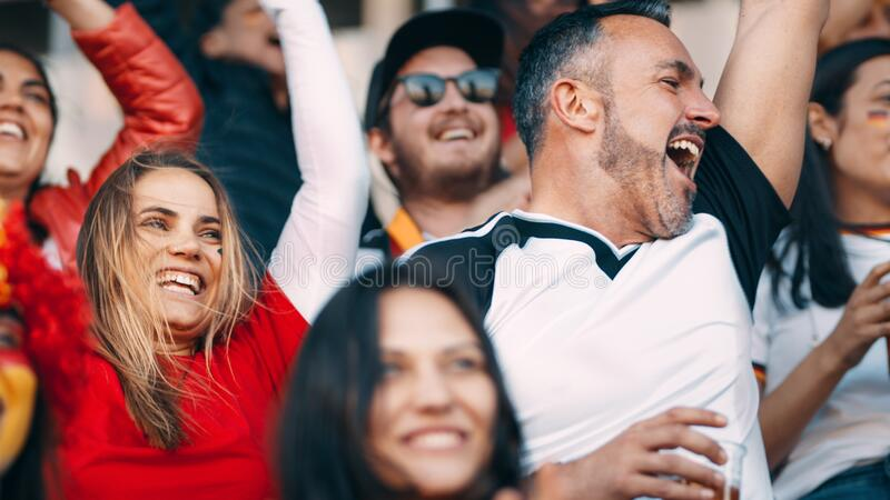 Excited crowd of sports fans cheering in stadium. Group of football fans watching a sport event and cheering. Excited crowd of sports fans cheering in stadium royalty free stock photos