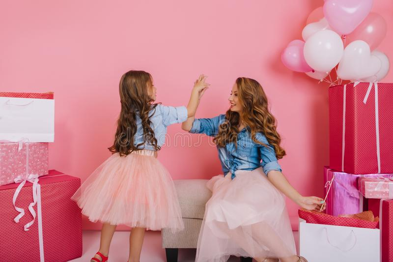 Excited curly girl giving high five to charming young mother before unpacking birthday presents. Adorable trendy mom and. Daughter playing together at children` royalty free stock image