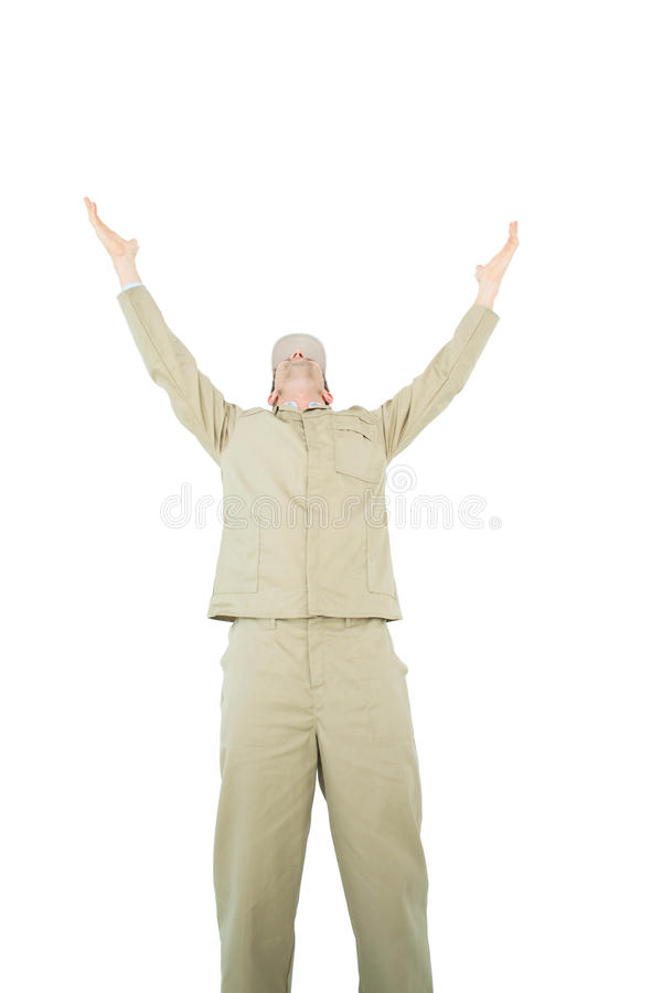 Excited delivery man with arms raised looking up. Against white background royalty free stock image