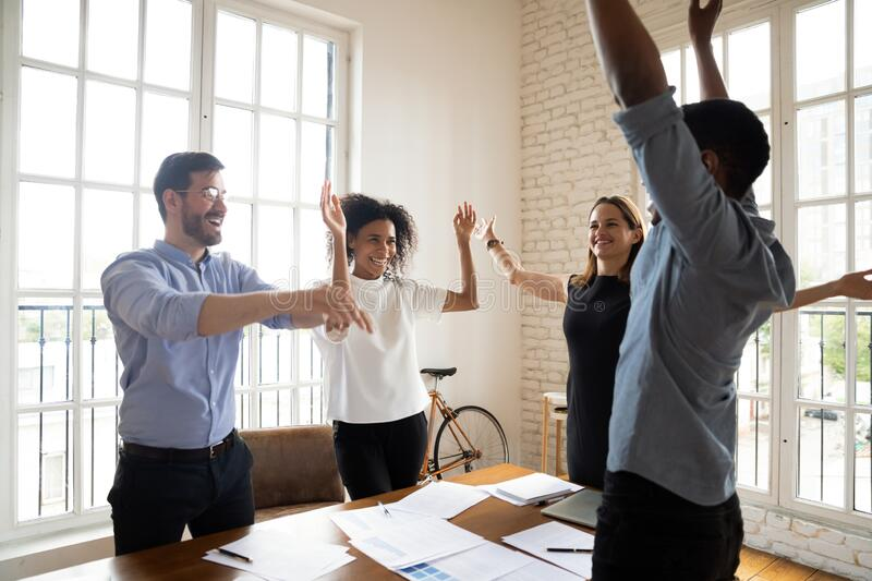 Excited diverse business people celebrating business achievement at meeting stock image