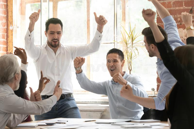 Excited diverse colleagues celebrate team win in office. Multiracial overjoyed colleagues employees feel euphoric celebrate shared business win or victory at stock image