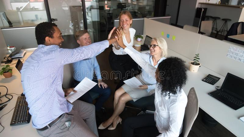 Excited diverse colleagues give high five motivated for success. Excited multiracial work team give high five having discussing at informal meeting at workplace royalty free stock image