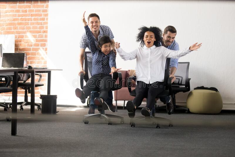 Excited diverse colleagues racing on chairs entertaining in office royalty free stock image