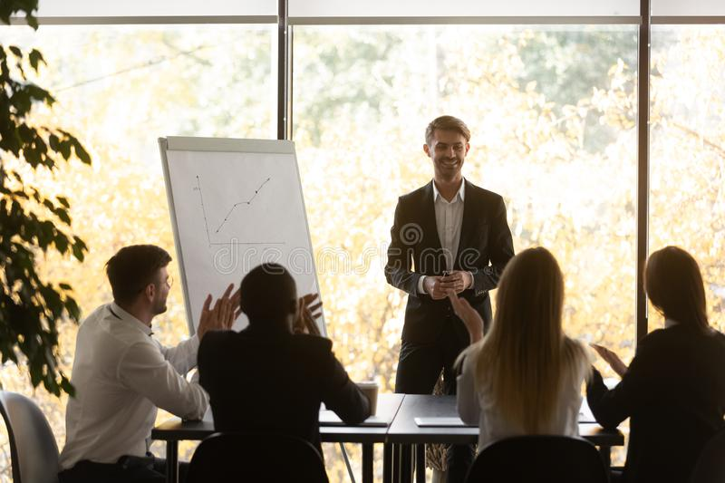 Excited diverse employees clap hands greeting male speaker stock photo