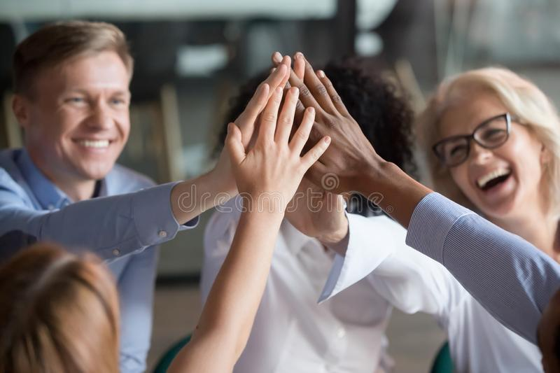 Excited diverse employees give high five motivated for success. Overjoyed diverse office workers give high five involved in teambuilding activity at meeting stock photos
