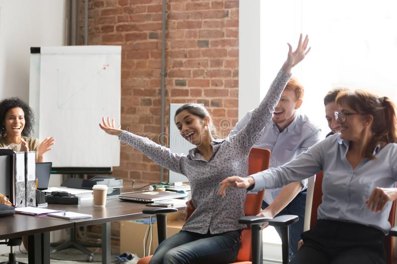 Excited diverse employees have fun riding chairs in office stock image