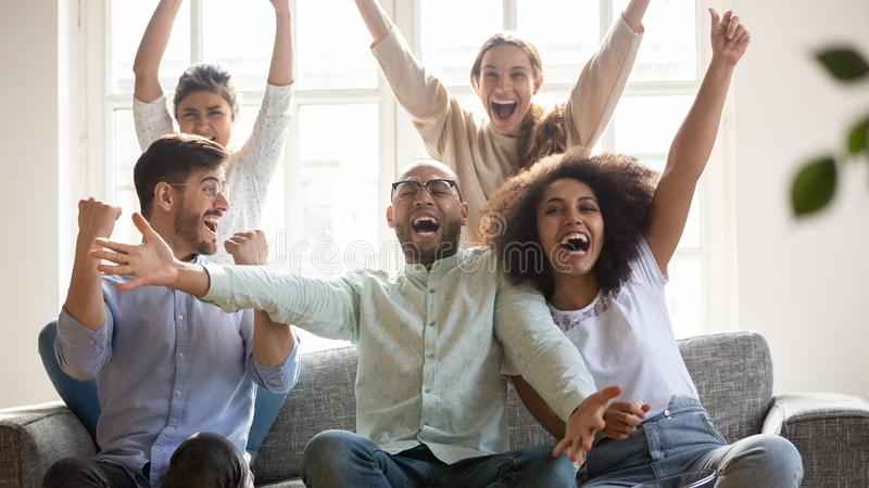 Excited diverse football fans celebrating win, screaming with joy stock photography