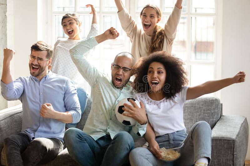 Excited diverse friends watching football match together, celebrating goal royalty free stock photography