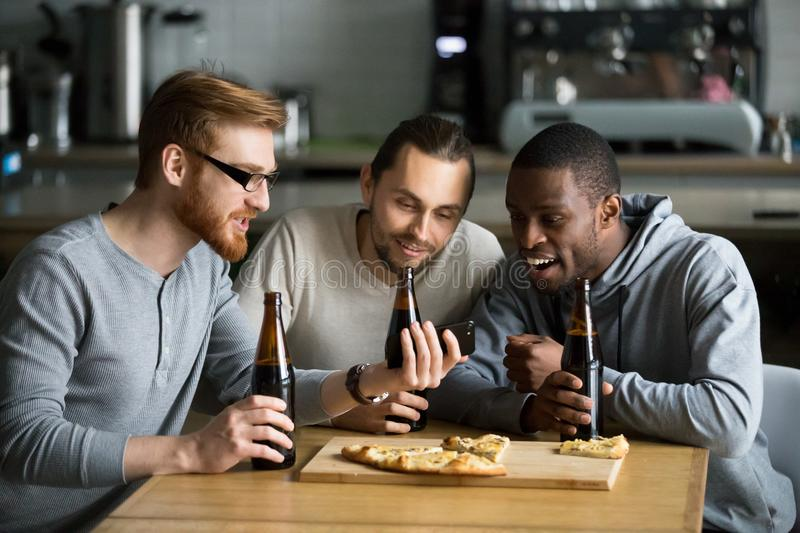 Diverse friends watching online video on smartphone drinking bee royalty free stock photography