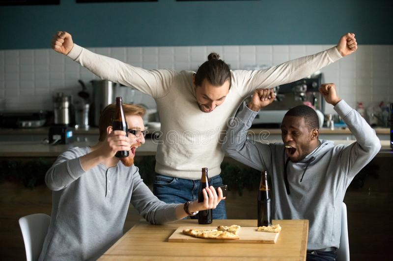 Ecstatic men celebrating victory watching game on smartphone, sp. Excited diverse men football fans celebrating victory goal score watching game online on stock image