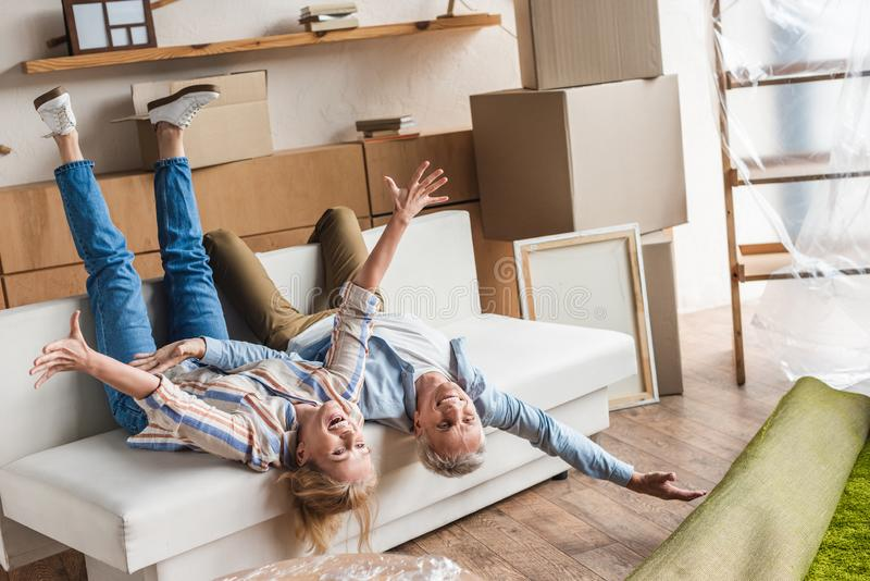 excited elderly couple lying on couch during relocation stock photos