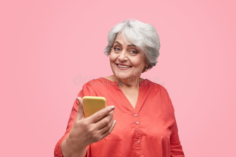Excited elderly female with smartphone royalty free stock images