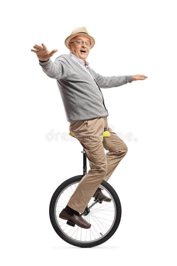 Excited elderly man riding a unicycle royalty free stock photo