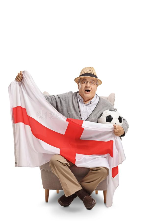 Excited elderly soccer fan sitting in an armchair and holding an royalty free stock images