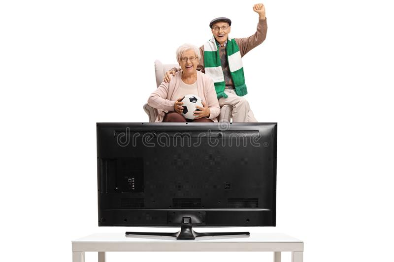Excited elderly soccer fans with a football and a scarf sitting stock photos