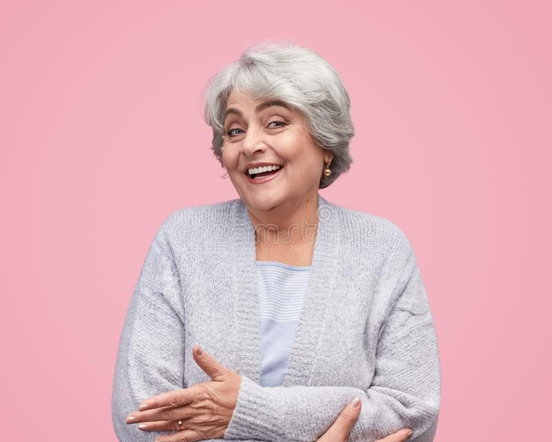 Excited elderly woman embracing herself royalty free stock image