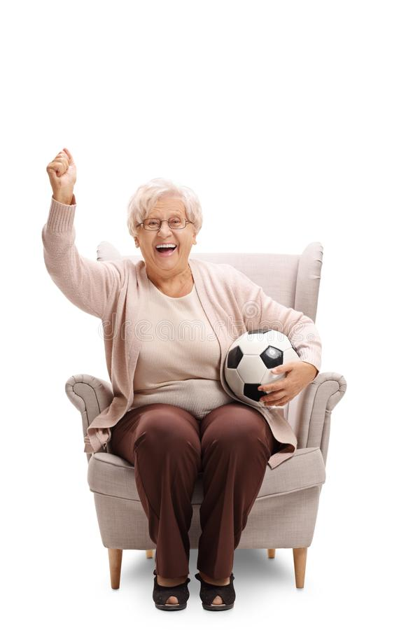 Excited elderly woman with a football sitting in an armchair and royalty free stock photos