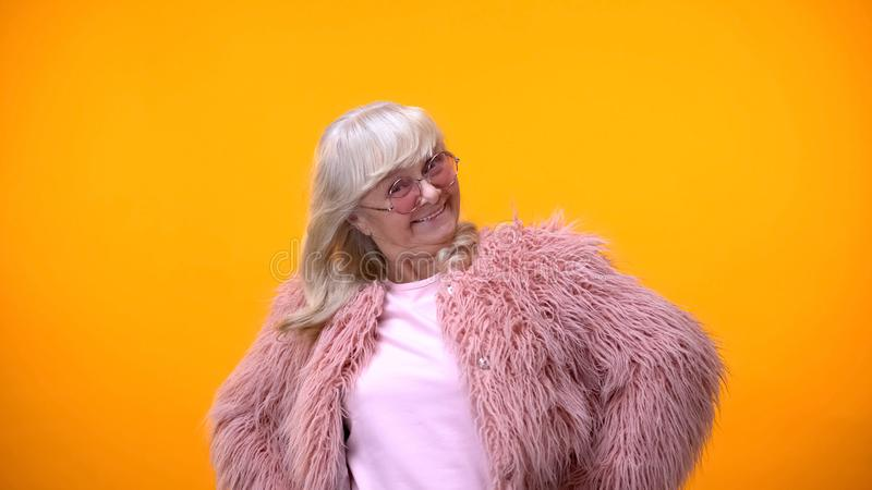 Excited elderly woman in pink coat and round sunglasses smiling into camera stock image