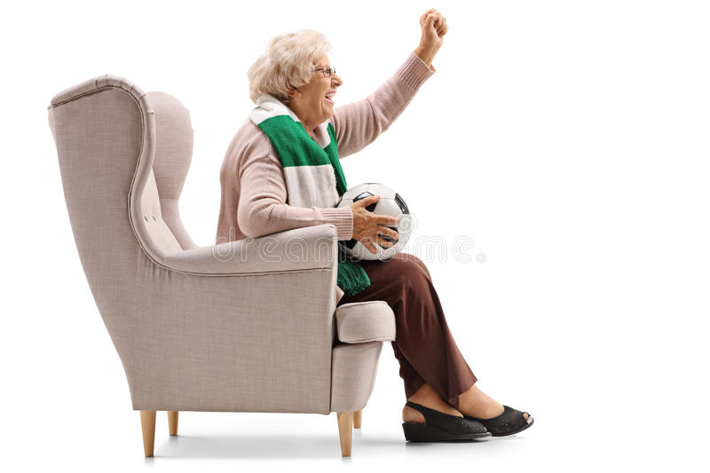 Excited elderly woman with a scarf and a football cheering royalty free stock photos