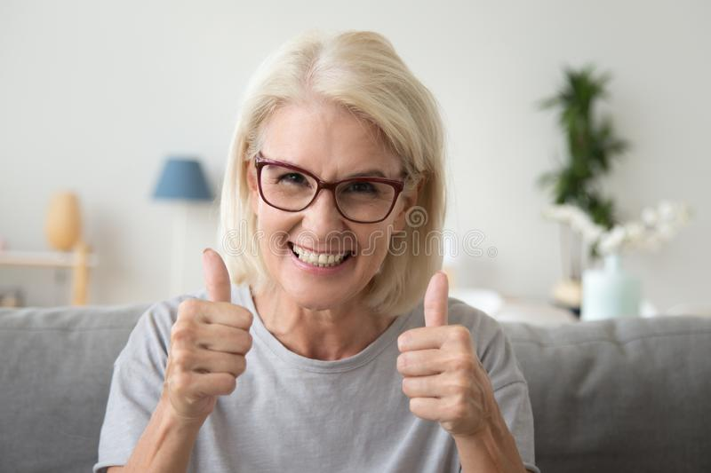 Excited elderly woman show thumbs up recommending something royalty free stock image