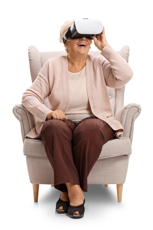 Excited elderly woman sitting in an armchair and using a VR headseat stock photos