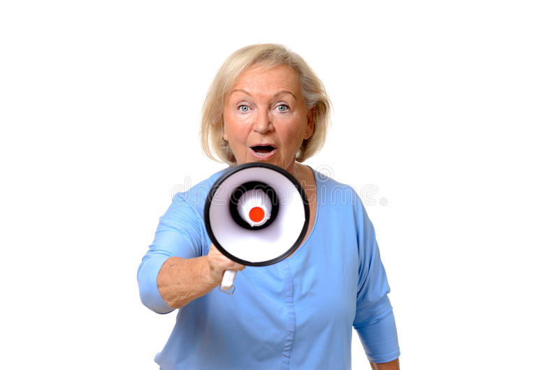 Excited elderly woman speaking into a megaphone. Conceptual of a protest, public speaking, rally or giving orders, upper body isolated on white stock photos
